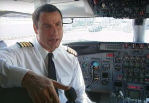 John Travolta jako pilot v kokpitu letadla